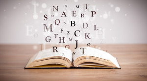 Opened book with flying letters on concrete background